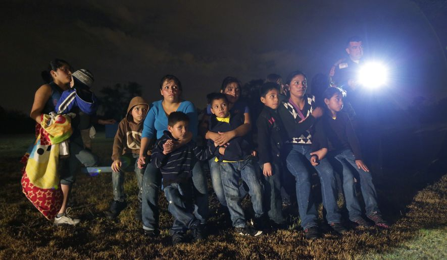 In this file photo, a group of immigrants from Honduras and El Salvador who crossed the U.S.-Mexico border illegally as they are stopped in Granjeno, Texas.  (AP Photo/Eric Gay, File) **FILE**