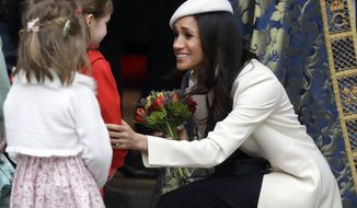 Meghan Markle receives flowers as she leaves after attending the Commonwealth Service at Westminster Abbey in London, Monday, March 12, 2018. Organised by The Royal Commonwealth Society, the Commonwealth Service is the largest annual inter-faith gathering in the United Kingdom. (AP Photo/Kirsty Wigglesworth, pool)