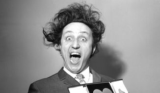 In this March 8, 1966, file photo, comedian Ken Dodd poses with his award for Show Business Personality of the Year, presented to him at the Variety Club's luncheon at the Savoy Hotel, London. British comedian Ken Dodd, whose seven-decade career stretched from the music-hall era to the age of social media, has died. He was 90. Publicist Robert Holmes says Dodd died Sunday, March 11, 2018 at his Liverpool home, the same house where he was born in 1927. (PA via AP, File)