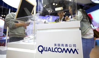 FILE - In this Thursday, April 27, 2017, file photo, visitors look at a display booth for Qualcomm at the Global Mobile Internet Conference (GMIC) in Beijing. On Monday, March 12, 2018, President Donald Trump blocked Singapore-based Broadcom's takeover of U.S. chipmaker Qualcomm on national security grounds. (AP Photo/Mark Schiefelbein, File)