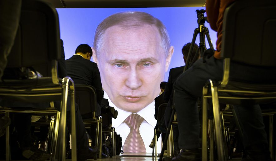 In this file photo taken Thursday, March 1, 2018, journalists watch as Russian President Vladimir Putin gives his annual state of the nation address in Manezh in Moscow, Russia. (AP Photo/Alexander Zemlianichenko, File)