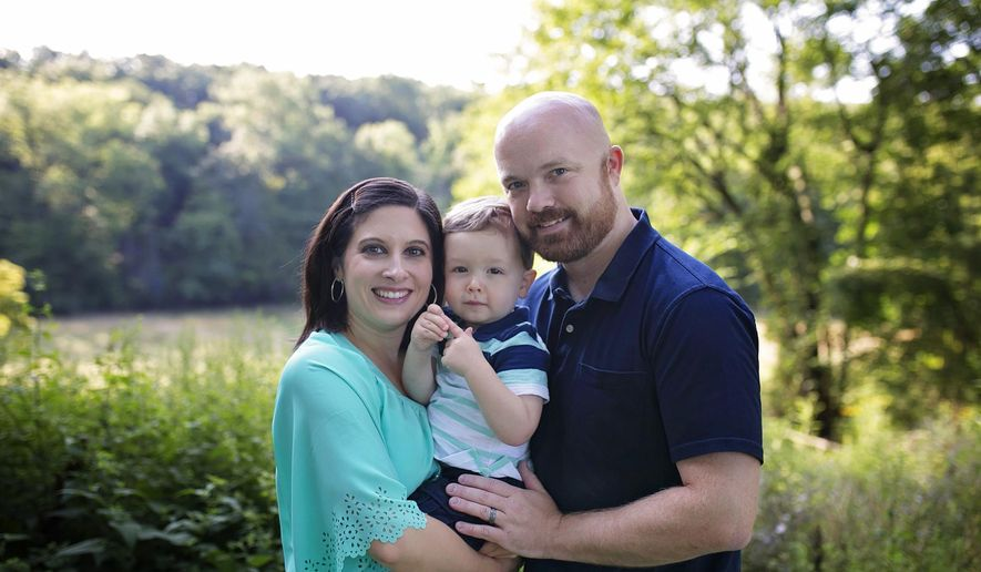 This undated photo shows Amber and Elliott Ash holding son, Ethan. The Ash's have filed a class action lawsuit against University Hospitals in Cleveland after its fertility clinic in suburban Cleveland discovered a storage tank malfunction March 4 and said last week that as many as 2,000 frozen eggs and embryos may have been damaged. (Ash family photo via AP)