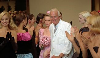 "In this July 11 1995, file photo, French designer Hubert de Givenchy is applauded by his models after his 1995-96 fall-winter haute couture fashion collection in Paris. French couturier Hubert de Givenchy, a pioneer of ready-to-wear who designed Audrey Hepburn's little black dress in ""Breakfast at Tiffany's,"" has died at the age of 91. (AP Photo/Lionel Cironneau)"