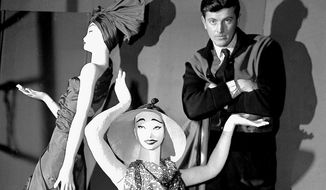 "FILE - In this Feb.1 1952 file photo, French fashion designer Hubert de Givenchy poses with mannequins in his shop in Paris. French couturier Hubert de Givenchy, a pioneer of ready-to-wear who designed Audrey Hepburn's little black dress in ""Breakfast at Tiffany's,"" has died at the age of 91. (AP Photo, File)"