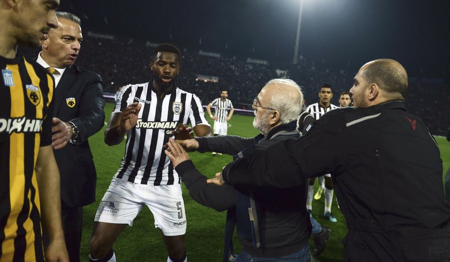 In this Sunday, March 11, 2018 photo, PAOK owner, businessman Ivan Savvidis, second right, approaches AEK Athens' Manager Operation Department Vassilis Dimitriadis, second left, as his bodyguard and PAOK's player Fernando Varela from Portugal, center, try to stop him during the Greek League soccer match between PAOK and AEK Athens in the northern Greek city of Thessaloniki. A disputed goal at the end of the Greek league match led to a pitch invasion by Savvidis, who appeared to be carrying a gun. (AP Photo)