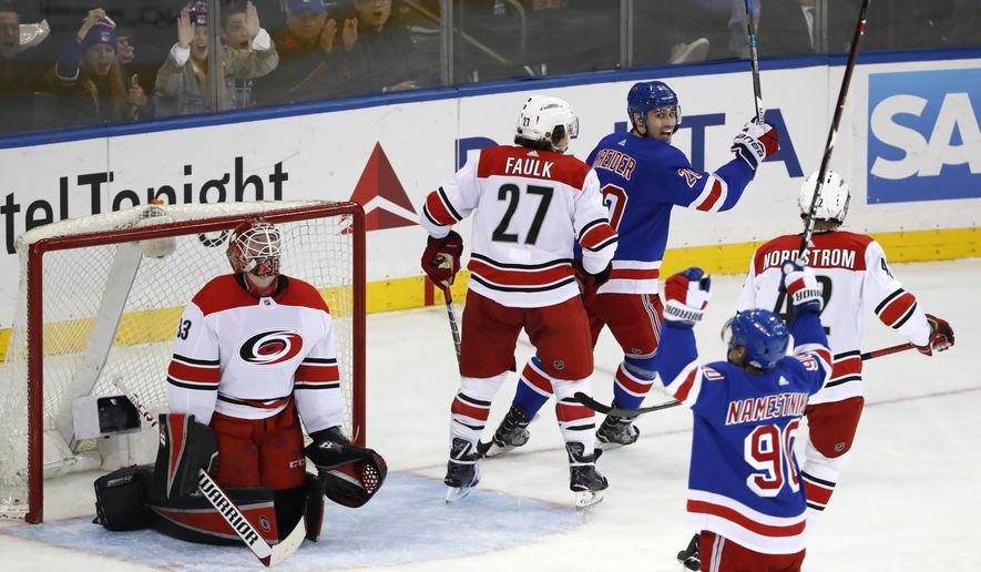 Carolina Hurricanes goaltender Scott Darling (33) reacts as New York Rangers center Vladislav Namestnikov (90), of Russia, and left wing Chris Kreider (20) celebrate Namestnikov's power play goal during the second period of an NHL hockey game in New York, Monday, March 12, 2018. Hurricanes defenseman Justin Faulk (27) and left wing Joakim Nordstrom (42), of Sweden, look on. (AP Photo/Kathy Willens)