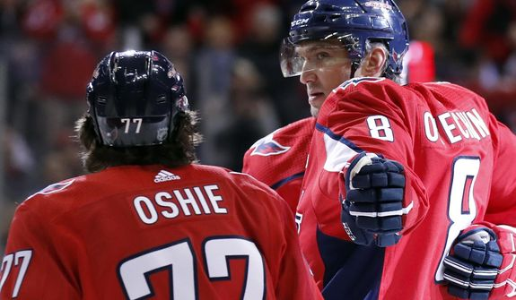 Washington Capitals left wing Alex Ovechkin (8) reaches to celebrate with right wing T.J. Oshie (77) after scoring in the first period of an NHL hockey game against the Winnipeg Jets, Monday, March 12, 2018, in Washington. (AP Photo/Alex Brandon)