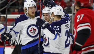 Winnipeg Jets' Patrik Laine (29) celebrates his goal with teammates Nikolaj Ehlers (27) and Paul Stastny (25) during the first period of an NHL hockey game against the Carolina Hurricanes, Sunday, March 4, 2018, in Raleigh, N.C. Laine had two goals in the 3-2 win. (AP Photo/Karl B DeBlaker)