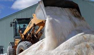 David Osgood, crew leader of the public works dept., mixes road salt, Monday, March 12, 2018, in Freeport, Maine. Much of the Northeast is bracing for blizzard conditions, a foot or more of snow and high winds as the third major nor'easter in 10 days bears down on the region. (AP Photo/Robert F. Bukaty)
