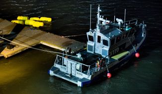 Yellow buoys that a New York police officer said are suspending a helicopter that crashed into the East River float next to a NYPD police boat at a pier in New York on Sunday, March 11, 2018. The helicopter crashed into New York City's East River Sunday night and flipped upside down in the water, killing at least a few people aboard and leaving some others in critical condition, officials said. (AP Photo/Andres Kudacki)