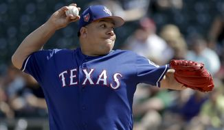 Texas Rangers starting pitcher Bartolo Colon throws against the Oakland Athletics during the first inning of a spring baseball game in Mesa, Ariz., Tuesday, March 6, 2018. (AP Photo/Chris Carlson)