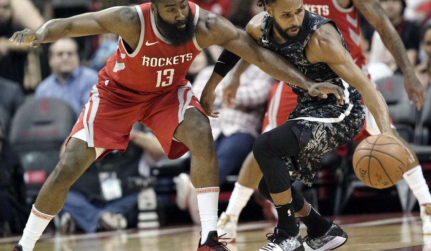 Houston Rockets' James Harden (13) tries to steal the ball from San Antonio Spurs' Patty Mills during the first half of an NBA basketball game Monday, March 12, 2018, in Houston. (AP Photo/David J. Phillip)