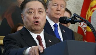 FILE - In this Thursday, Nov. 2, 2017, file photo, Broadcom CEO Hock Tan speaks while U.S. President Donald Trump listens, in background, during an event at the White House in Washington, to announce the company is moving its global headquarters to the United States. In a decision announced Monday, March 12, 2018, Trump is blocking Singapore chipmaker Broadcom from pursuing a hostile takeover of U.S. rival Qualcomm on the grounds that the combination would threaten national security. (AP Photo/Evan Vucci, File)