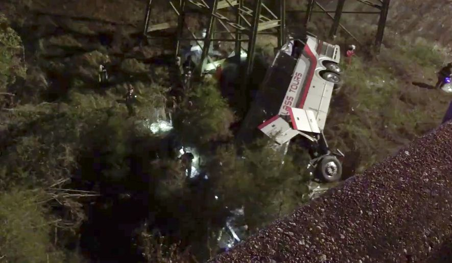 This photo provided by Jesus Tejada shows first responders searching around a bus that plunged into a ravine, Tuesday, March 13, 2018 on Interstate 10, Loxley, Ala. Several people were on board, and all of them were brought to 10 hospitals in Alabama and Florida, either by helicopter or ambulance, said Baldwin County Sheriff Huey Hoss Mack.  (Jesus Tejada via AP)