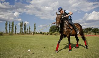 In this Feb. 27, 2018 photo, Jed Hulsey, from Newport Beach, California, hits the ball during a polo practice at La Carona club, Capilla del Senor, Buenos Aires province, Argentina. Polo has traditionally been an exclusive, glamorous sport reserved for the rich elite. But in Argentina, home to the world's top polo players, tourists can ride horses, learn how to hit the wooden ball from the pros, and even play a match in a real field. (AP Photo/Victor R. Caivano)