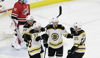Boston Bruins' David Pastrnak (88), of the Czech Republic, is congratulated by Riley Nash (20), Brad Marchand (63) and Brandon Carlo (25) following Pastrnak's goal against Carolina Hurricanes goalie Cam Ward (30) during the third period of an NHL hockey game in Raleigh, N.C., Tuesday, March 13, 2018. Boston won 6-4. (AP Photo/Gerry Broome)