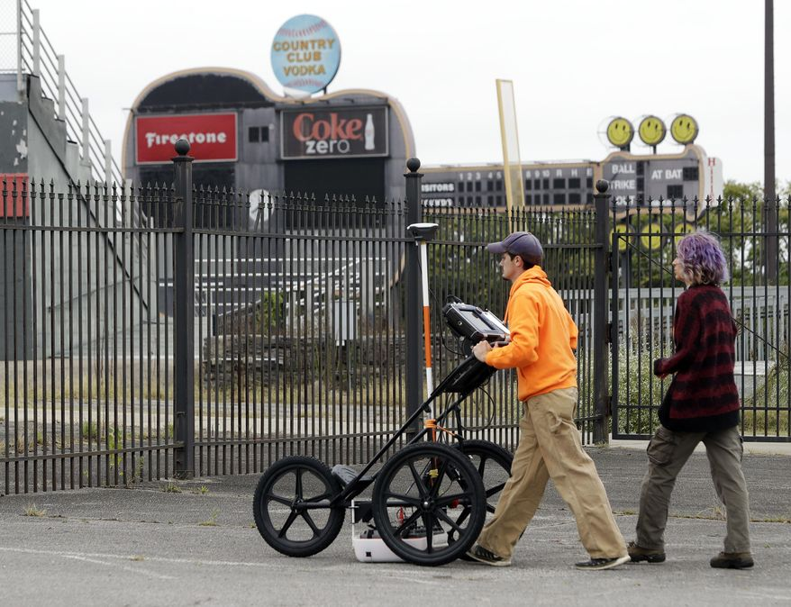 FILE - In this Oct. 12, 2017 photo, Greer Stadium, field technicians Chandler Burchfield, left, and Cristina Oliveira use ground penetrating radar in the parking lot of Greer Stadium, a former minor-league baseball park, in Nashville, Tenn. Nashville Mayor David Briley says his city can begin to acknowledge, atone and seek reconciliation for slavery by replacing the unused minor league baseball stadium with a park commemorating a Civil War fort built by slaves. Briley announced Tuesday, March 13, 2018,  he'll seek $1 million in city money to demolish Greer Stadium. (AP Photo/Mark Humphrey, File)