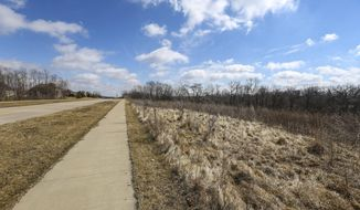 This Wednesday, March 7, 2018 photo shows a vacant 18-acre lot alongside Tanglefoot Lane in Bettendorf, Iowa, between Devils Glen and Middle roads. The property was previously used as a landfill site and is causing the surrounding area to undergo environmental testing because of contamination found on site. (Andy Abeyta/Quad City Times via AP)