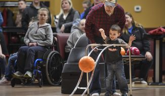 In this Saturday, March 10, 2018, photo, Michael Coffman helps his son Wesley during a Super Strikers bowling event at Great River Bowl in Sartell, Minn. (Dave Schwarz/St. Cloud Times via AP)