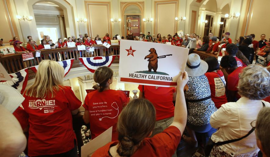 FILE - In this June 28, 2017 file photo, members of the California Nurses Association and supporters rally on the second floor rotunda at the Capitol calling for a single-payer health plan in Sacramento, Calif. A panel created by Assembly Speaker Anthony Rendon to study improvements to California's health care system rejected adopting single-payer in a report released Tuesday, March 13, 2018, but said the Legislature could hire new staff to develop a long-term plan for government-run health care. (AP Photo/Rich Pedroncelli, File)