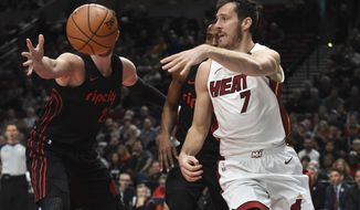 Miami Heat guard Goran Dragic passes the ball on Portland Trail Blazers center Jusuf Nurkic during the first half of an NBA basketball game in Portland, Ore., Monday, March 12, 2018. (AP Photo/Steve Dykes)