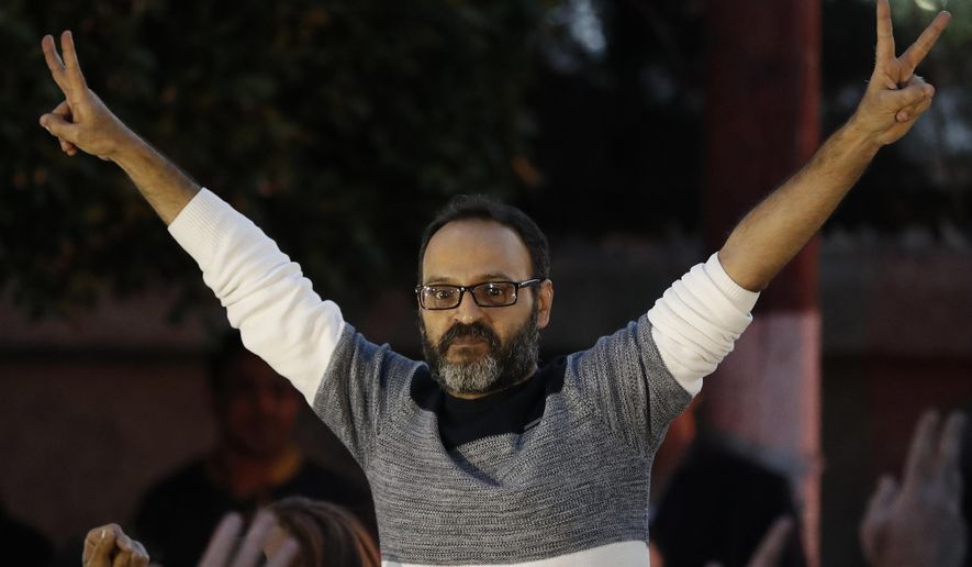 A Lebanese stage actor Ziad Itani, who was indicted on charges of collaborating with Israel and drug possession, flashes the victory signs after he was released by Lebanese authorities, on his arrival to his house, in Beirut, Lebanon, Tuesday, March 13, 2018. Itani was released on Tuesday and cleared of charges, while the officer who built the case against him was ordered detained. (AP Photo/Hussein Malla)