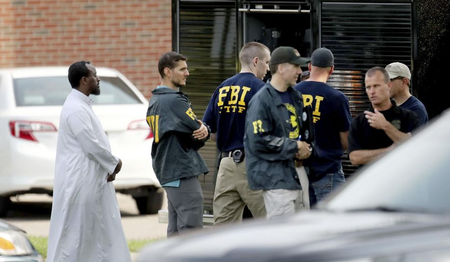 """In this Aug. 15, 2017, file photo, law enforcement officials investigate an explosion at the Dar Al-Farooq Islamic Center in Bloomington, Minn. Federal authorities said Tuesday, March 13, 2018, they have charged three men from rural central Illinois with the bombing of a Minnesota mosque last year and one of the men told an investigator the goal of the attack was to """"scare"""" Muslims out of the United States. A statement from the U.S. attorney's office in Springfield, Illinois, says the men also are suspected in the attempted bombing of an abortion clinic in November. (David Joles/Star Tribune via AP File)"""