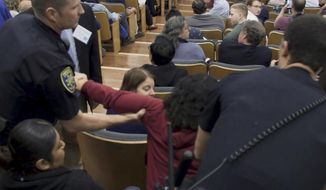 In this image made from a Feb. 26, 2018, video released by the University of California, Los Angeles, a woman is removed from the audience who was listening to U.S. Treasury Secretary Steve Mnuchin speak at UCLA. The previously withheld video has been released showing the near-constant heckling of Mnuchin during the moderated talk about the economy at UCLA. The video shows audience members hissing at Mnuchin throughout the event. The hissing was so loud the secretary barely spoke a sentence without commenting about it. (UCLA via AP)