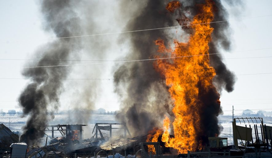 Fires burn after a propane explosion at a residence north of Helena, Mont., on Tuesday, March 13, 2018. A man suffered burns and a garage was destroyed in the incident. (Thom Bridge/Independent Record via AP)