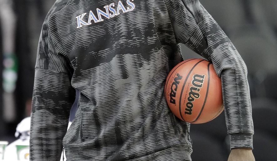 FILE - In this March 7, 2018, file photo, injured Kansas center Udoka Azubuike watches while his team practices for an NCAA college basketball game in the Big 12 basketball tournament in Kansas City, Mo. The success or failure of the teams from the Sunflower State in the NCAA Tournament might be decided not by the players but their trainers. Top-seeded Kansas hopes to get injured center Udoka Azubuike back Thursday, and No. 9 seed Kansas State hopes to have stars Barry Brown and Dean Wade available Friday. (AP Photo/Orlin Wagner, File)
