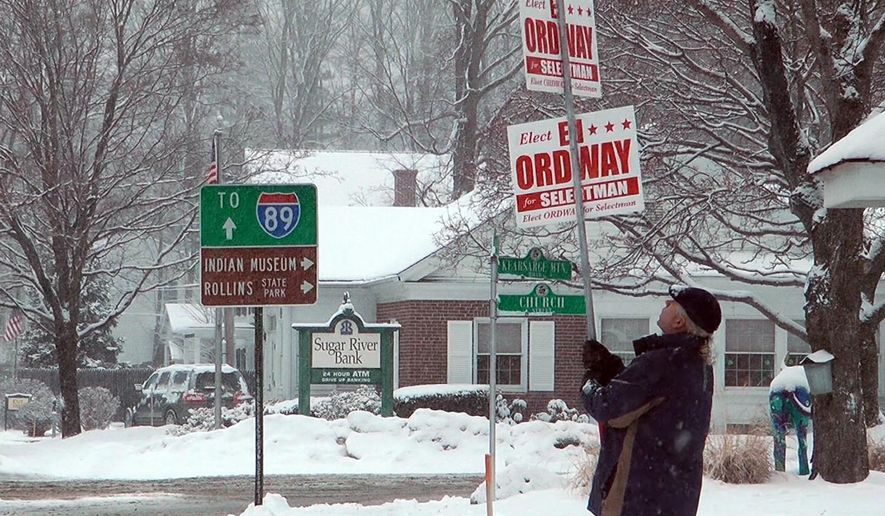 Ed Ordway, a candidate for the Board of Selectman in Warner, N.H., holds a campaign sign outside Town Hall on Tuesday, March 13, 2018. Last year, when a storm also coincided with Town Meeting Day, nearly 80 communities postponed their elections. (AP Photo/Holly Ramer)