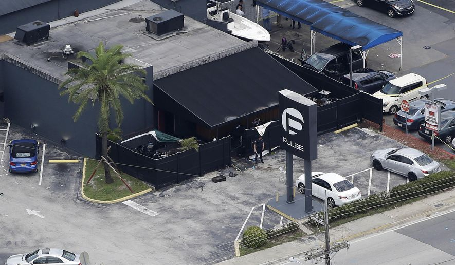 FILE - In this June 12, 2016 file photo, law enforcement officials work at the Pulse nightclub in Orlando, Fla., following a mass shooting. The widow of the gunman who killed dozens of people at the Pulse nightclub in Orlando is going on trial Wednesday, March 14, 2018, in federal court. Thirty-one-year-old Noor Salman is charged with aiding and abetting her deceased husband Omar Mateen in planning the 2016 attack on the Pulse nightclub. (AP Photo/Chris O'Meara, File)