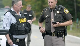 """In this Sept. 27, 2017 photo, Isabella County Sheriff Michael Main, right, coordinates efforts in a police manhunt in rural Isabella County, Mich. Main is apologizing for accidentally leaving his gun in a mid-Michigan school gym locker room. Main said Tuesday, March 13, 2018 he takes full responsibility and is """"devastated"""" by his own negligence. He says he was at a weekend event at Shepherd Middle School and used the locker room to change into uniform. (Lisa Yanick Litwiller /The Morning Sun via AP)"""