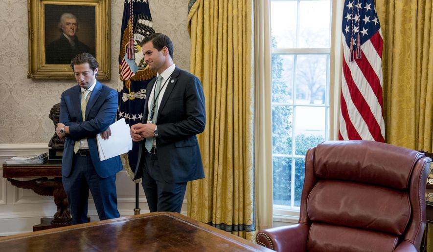 FILE - In this Jan. 31, 2018 file photo, White House aide John McEntee, right, and Treasury Secretary Steve Mnuchin's Chief of Staff Eli Miller, left, stand in the Oval Office as President Donald Trump speaks at a tax reform meeting with American workers at the White House in Washington. Trump's personal aide is leaving the White House and will rejoin his campaign.  (AP Photo/Andrew Harnik)