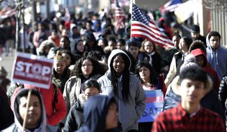 Diamond Bryant, center, a freshman at James Ferris High School walks with classmates during a student walkout, Wednesday, March 14, 2018, in Jersey City, N.J. Students across the country participated in walkouts Wednesday to protest gun violence, one month after the deadly shooting inside a high school in Parkland, Fla. (AP Photo/Julio Cortez)