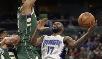 Orlando Magic's Jonathon Simmons (17) goes to the basket against Milwaukee Bucks' Jabari Parker during the second half of an NBA basketball game Wednesday, March 14, 2018, in Orlando, Fla. (AP Photo/John Raoux)
