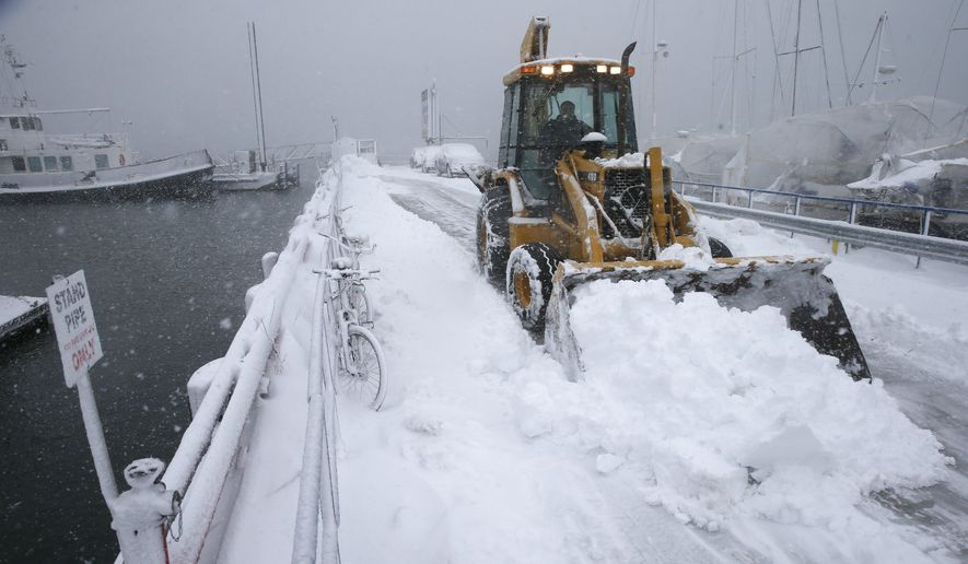 A front end loader clears the pier at the Boston Harbor Shipyard and Marina in Boston, Tuesday, March 13, 2018. Boston finds itself in the bullseye of the third nor'easter in two weeks, with forecasters warning of up to 18 inches of snow and 2 feet or more to the south. (AP Photo/Michael Dwyer)