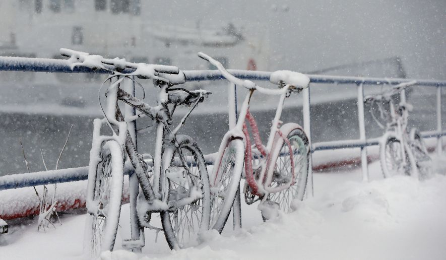 Bicycles are chained to a railing are covered with snow at the Boston Harbor Shipyard and Marina in Boston, Tuesday, March 13, 2018.  The National Weather Service issued a blizzard warning for much of the coast of Maine, New Hampshire, and Massachusetts.  (AP Photo/Michael Dwyer)