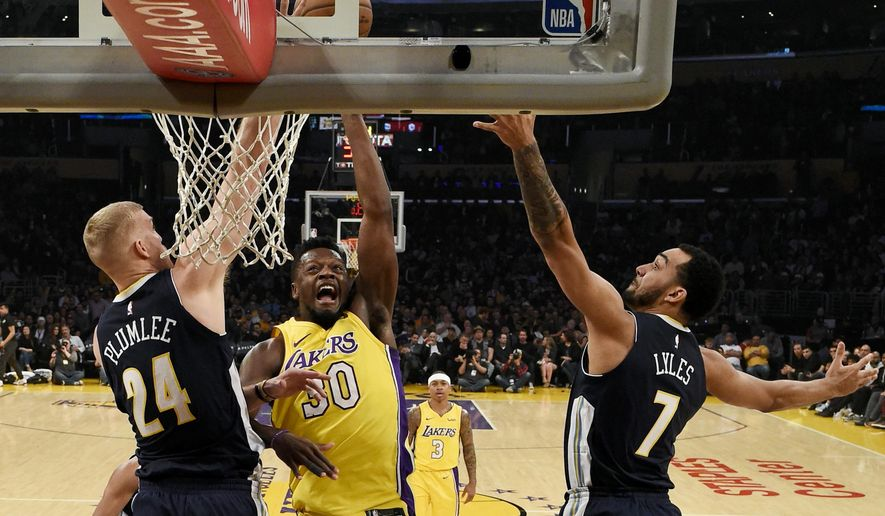 Los Angeles Lakers forward Julius Randle, center, attempts a shot while Denver Nuggets center Mason Plumlee, left, and forward Trey Lyles defend during the first half of an NBA basketball game in Los Angeles, Tuesday, March 13, 2018. (AP Photo/Kelvin Kuo)
