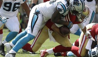 FILE - In this Sunday, Sept. 10, 2017 file photo, Carolina Panthers defensive end Julius Peppers (90) tackles San Francisco 49ers quarterback Brian Hoyer during the first half of an NFL football game in Santa Clara, Calif. The Panthers have announced they have re-signed free agent defensive end Julius Peppers to a one-year contract. A person familiar with the situation says the deal is for $5 million, with $2.5 million guaranteed. The person spoke to The Associated Press on Wednesday, March 14, 2018,  on condition of anonymity because the team does not release financial terms of contracts. (AP Photo/Marcio Jose Sanchez, File)