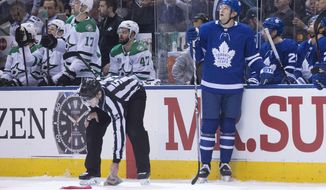 Toronto Maple Leafs left wing James van Riemsdyk (25) looks up at the screen as a referee pucks up hats thrown onto the ice after van Riemsdyk scored a hat trick against the Dallas Stars, during the third period of an NHL hockey game Wednesday, March 14, 2018, in Toronto. (Chris Young/The Canadian Press via AP)