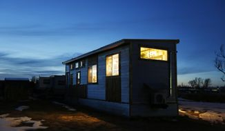 In this Wednesday, Feb. 28, 2018 photo, the Johnson family's tiny house glows just after sunset west of Casper, Wyo. The family of four moved into the 360-square-foot house in October 2017. (Alan Rogers/The Casper Star-Tribune via AP)