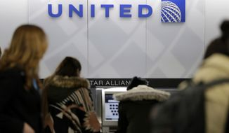 In this March 15, 2017, photo, people stand in line at a United Airlines counter at LaGuardia Airport in New York. A dog died on a United Airlines plane after a flight attendant ordered its owner to put the animal in the plane's overhead bin. United said Tuesday, March 13, 2018, that it took full responsibility for the incident on the Monday night flight from Houston to New York. (AP Photo/Seth Wenig, File)