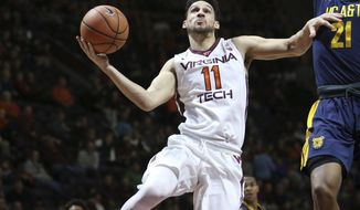 FILE - In this Dec. 28, 2017, file photo, Devin Wilson (11) of Virginia Tech drives past North Carolina A&T's Japhet Kadji (21) in the second half of an NCAA college basketball game in Blacksburg Va. Wilson's basketball career at Virginia Tech has been circuitous to say the least. The senior point guard has had his share of ups and downs. But lately he has been trending in a positive direction for the Hokies, who couldn't be happier with his play. (Matt Gentry/The Roanoke Times via AP, File)