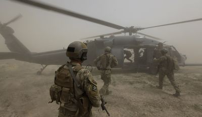 """In this July 29, 2010, file photo, Air Force Pararescuemen, or """"PJs,"""" of the 58th Rescue Squadron, secure a landing zone for their Pave Hawk helicopter during a rescue mission for a wounded Afghan policeman, during an ongoing firefight with the Taliban in the Arghandab Valley, Kandahar province, southern Afghanistan. The PJs and helicopter aircrews are part of the U.S. Air Force's 451st Air Expeditionary Wing based at Kandahar Air Field, which provides a variety of air assets in southern Afghanistan. (AP Photo/Brennan Linsley, File)"""
