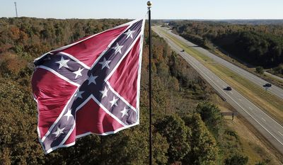 This Friday, Oct. 27, 2017 shows traffic flowing along the Route 58 bypass as a giant Confederate battle flag owned by flagger Robert Collie flutters in the breeze in Danville, Va. (AP Photo/Steve Helber)