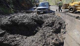 Workers prepare to free a trapped car from tons of debris after mudslides from heavy rain overnight caused the closure of Topanga Canyon Boulevard, a key mountain highway over the Santa Monica Mountains, above Malibu, Calif., early Thursday, March 15, 2018. No injuries were reported. The California Department of Transportation said that with more rain expected, the route through Topanga Canyon will remain closed through at least Sunday night. (AP Photo/Reed Saxon)