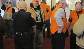 FILE - In this Tuesday, March 13, 2018 file photo, several gun-rights activists wearing blaze orange hunting vests visit the Vermont Statehouse in Montpelier, Vt., where bills are under consideration to place restrictions on gun ownership. A nationwide review of state legislation by The Associated Press suggests the Florida high school shooting may not lead to the sea change in firearms policy that gun-control advocates had desired. People on both sides of the debate are watching developments in gun-friendly Vermont, where Republican Gov. Phil Scott abandoned his stance against gun control after police arrested an 18-year-old man allegedly plotting a mass shooting at a high school. (AP Photo/Wilson Ring, File)