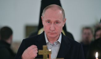 In this Friday, Jan. 19, 2018, file photo, Russian President Vladimir Putin crosses himself during a Orthodox Epiphany service in St. Nilus Stolobensky Monastery on Lake Seliger in Svetlitsa village, Russia. President Vladimir Putin seems self-assured and confident of victory in the election on Sunday, March 18, even as the Kremlin works hard to bolster turnout to make the result as impressive as possible. (Alexei Druzhinin, Sputnik, Kremlin Pool Photo via AP, file)