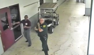 This Feb. 14, 2018, frame from security video provided by the Broward County Sheriff's Office shows deputy Scot Peterson, right, outside Marjory Stoneman Douglas High School in Parkland, Fla. The video released Thursday, March 15, shows Peterson going toward the high school building while a gunman massacred 17 students and staff members, but stayed outside with his handgun drawn. (Courtesy of the Broward County Sheriff's Office via AP)
